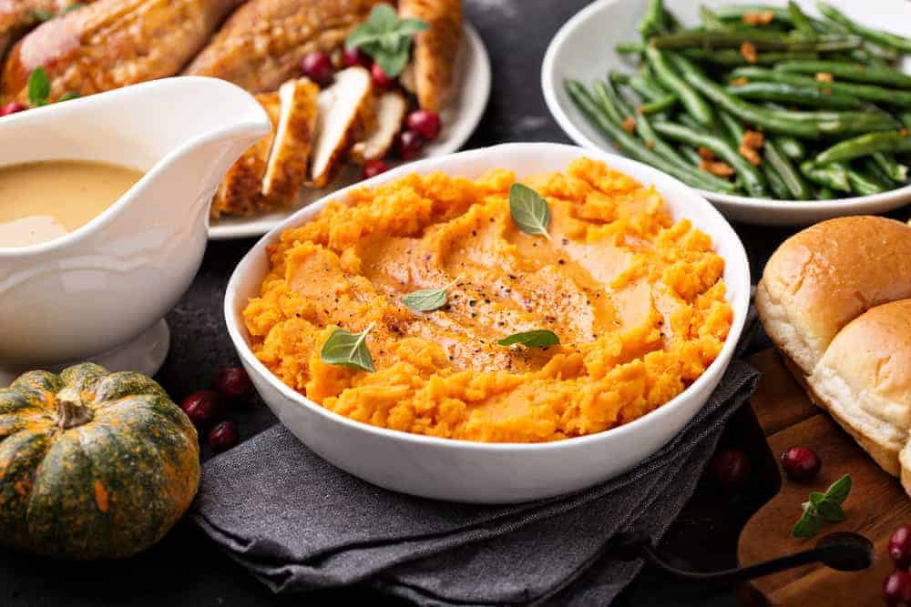 mashed sweet-potatoes-fresh-thyme-thanksgiving-side-dish in white bowl | kimschob.com